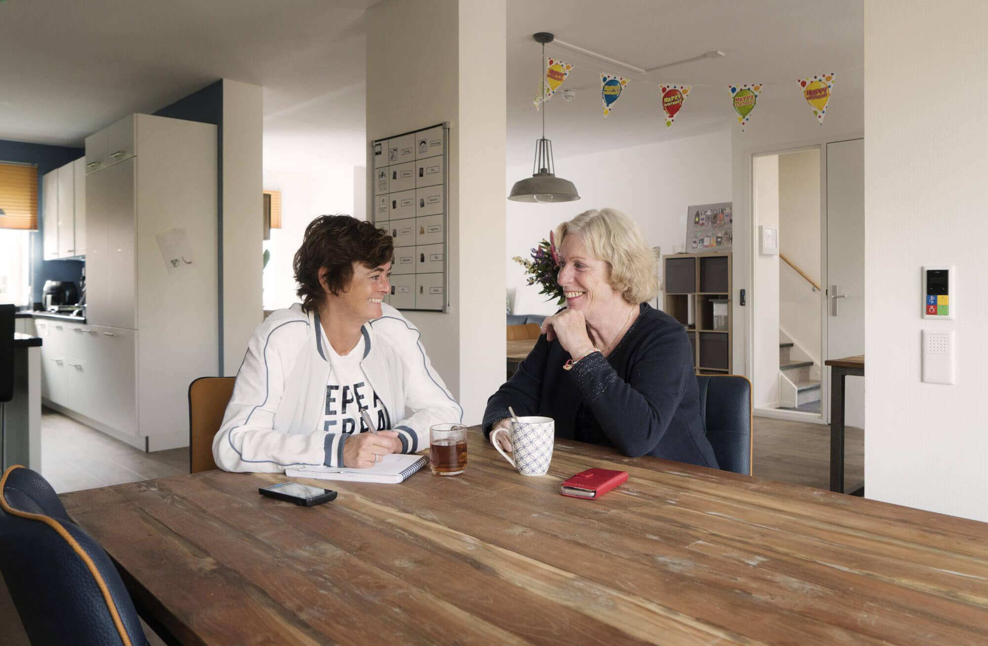 Karin Verbaarschot en Maria Vermeeren in de gemeenschappelijke woonkamer en Keuken bij Stichting Anderdak