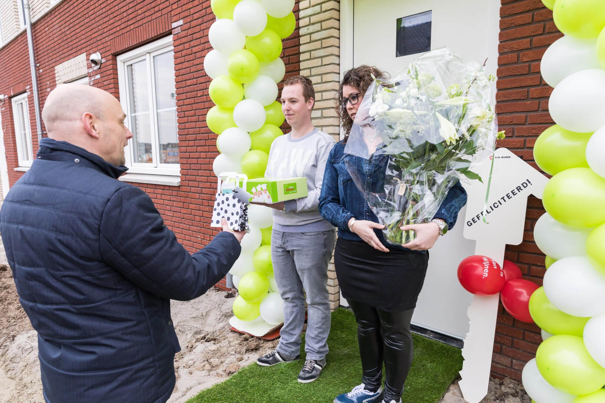 Pim en Gladys ontvangen taart en bloemen van wethouder Gerrie Elfrink
